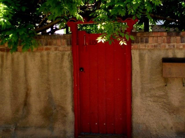 """Red door on Roque Tudesque House in Santa Fe, New Mexico"""