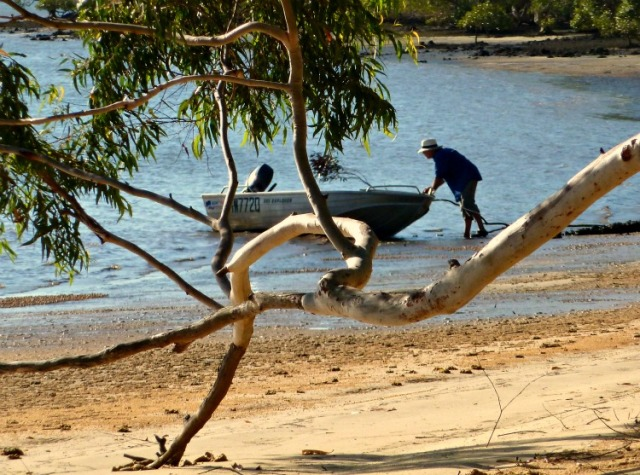 """Life on an island in the bay off Brisbane: pusing the tinny off the beach"""
