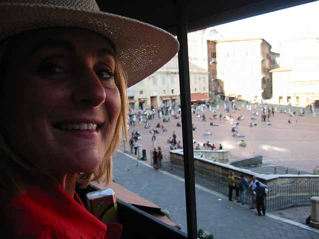 """Seated on a tiny balcony outside a third story pub with the best view of the Campo, Siena, Italy"""